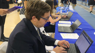 Student signing in at Career Fair on a laptop.
