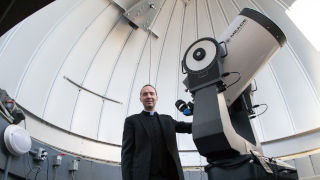 Photo of Father Laracy in front of a telescope