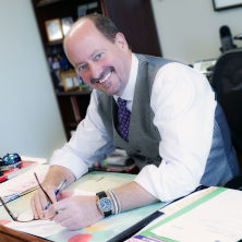 David E. Baugh sitting at desk