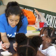 Seton Hall student May Lin drawing with three children
