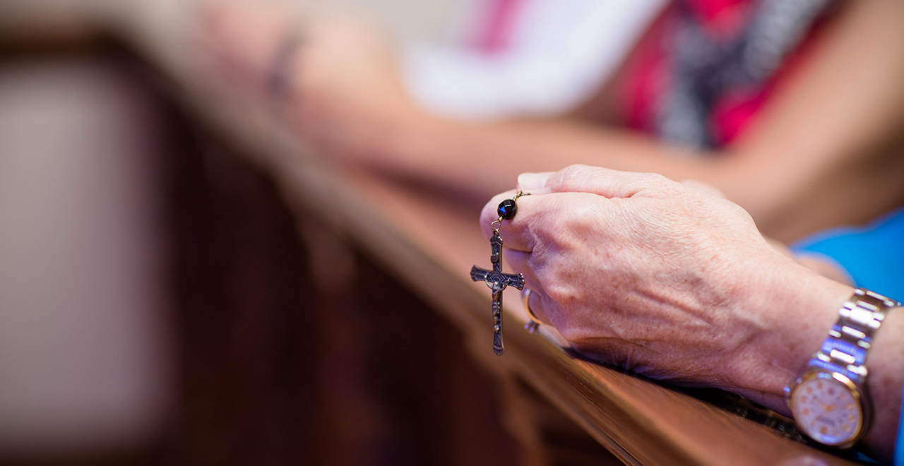 A person holding a rosary in prayer.