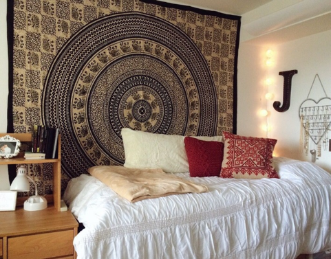 Photo of a dorm room with a tapestry on the wall.
