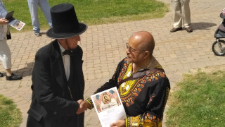 Rev. Forrest Pritchett shaking hands with Abraham Lincoln while holding a document of the Emancipation Proclamation.