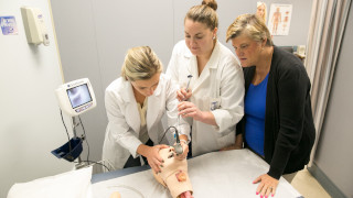 Nursing students work on a mannequin